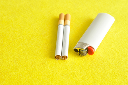 A white lighter with two cigarettes displayed on a yellow background Stock Photo