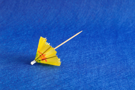 cocktail umbrella: A yellow cocktail umbrella isolated on a blue background Stock Photo