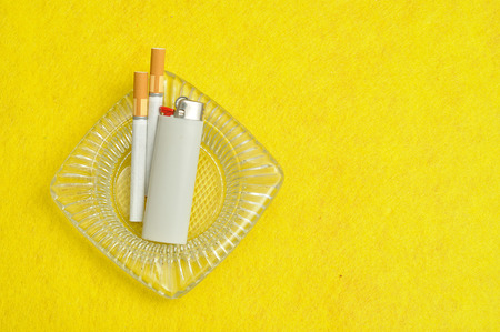 narcotic: An ashtray displayed with two cigaretts and white lighter on a yellow background
