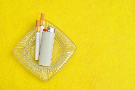 encendedores: Un cenicero está representada con dos cigaretts y blanco más claras sobre un fondo amarillo