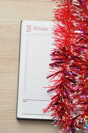 december 25th: Diary open on the 25th of December decorated with Tinsel Stock Photo