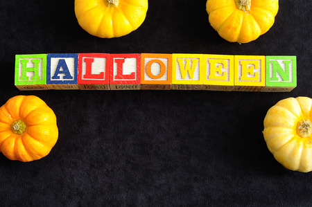 spelled: Halloween spelled with alphabet blocks with pumpkins against a black background
