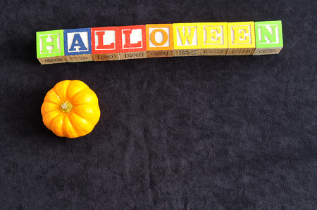 spelled: Halloween spelled with alphabet blocks with a pumpkin against a black background Stock Photo