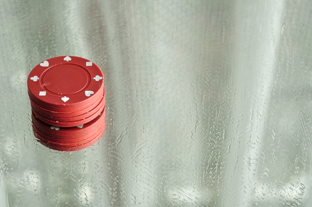 gamblers: A stack of poker chips reflecting in a mirror that is stained with water drops Stock Photo