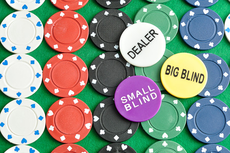 Rows of poker chips with a dealer, big blind and small blind chips displayed on top