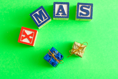spelled: Xmas spelled with Alphabet blocks on a green background with two shiny gifts Stock Photo