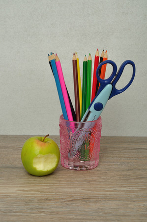 filled out: A glass filled with coloring pencils and a scissor displayed on a table with an apple with a bite taken out against a white background Stock Photo