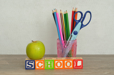 The word school spelled with colorful alphabet blocks displayed with a glass filled with coloring pencils and a scissor and a green apple on a table with a white background
