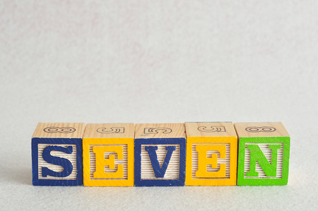 spelled: The word seven (7) spelled with colorful alphabet blocks isolated against a white background