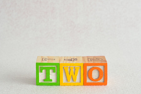 spelled: The word two (2) spelled with colorful alphabet blocks isolated against a white background