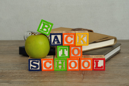 spelled: The words back to school spelled with colorful alphabet blocks displayed with a green apple and a stack of books on a table with a white background Stock Photo