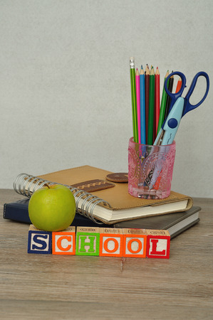 spelled: The word school spelled with colorful alphabet blocks displayed with a glass filled with coloring pencils and a scissor and a green apple on a table with a white background