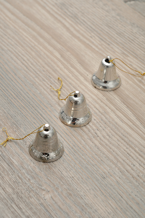 silver bells: Silver bells to decorate a Christmas tree isolated against a wooden background Stock Photo