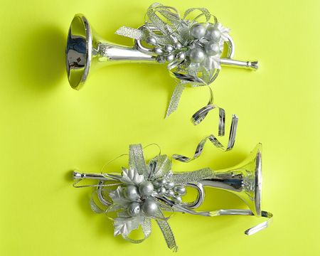 trumpets: Silver trumpets to decorate a Christmas tree isolated against a yellow background