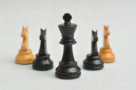 pensamiento estrategico: A black king with the four knight pieces on a white background. Shallow depth of field