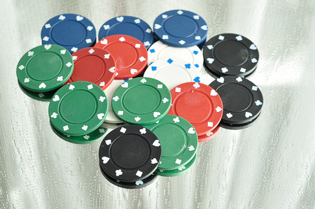 gambler: A stack of poker chips reflecting in a mirror that is stained with water drops Stock Photo