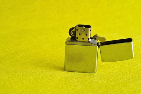 encendedores: Un encendedor de plata aislado en un fondo amarillo Foto de archivo