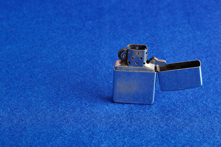 gas lighter: A silver lighter isolated on a blue background