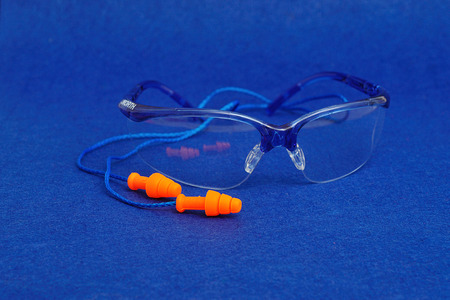 precaution: Safety goggles and ear plugs isolated on a blue background