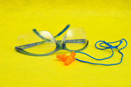 safety goggles: Safety goggles and ear plugs isolated on a yellow background Stock Photo