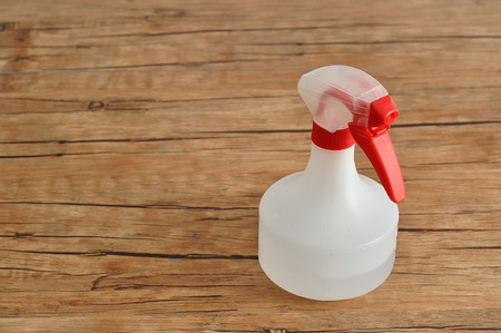 trigger: A white spray bottle with a red trigger isolated against a wooden background Stock Photo