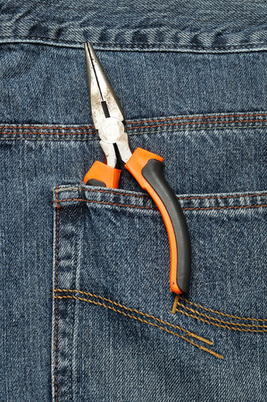 long nose: A set of long nose pliers in the back pocket of a denim jeans pant