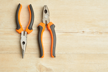 long nose: A long nose pliers and a pliers isolated on a wooden background