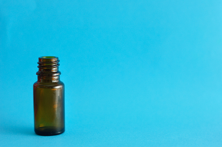 brown bottle: A small brown bottle isolated on a blue background