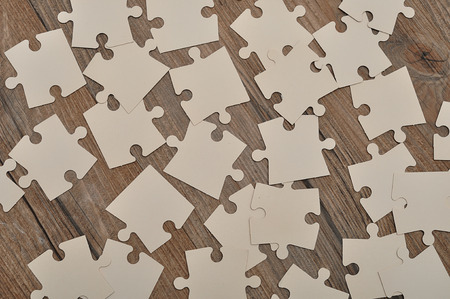 disharmony: White puzzle pieces on a wooden background