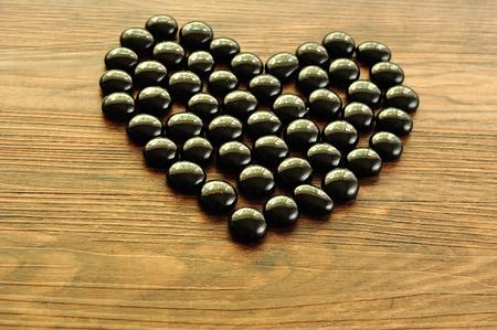 black pebbles: Heart make out of black pebbles Stock Photo