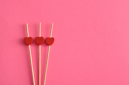 saint valentine   s day: Valentines Day. Three red hearts on sticks with a pink background
