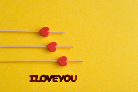 saint valentine   s day: Valentines Day. Three red hearts on sticks with a yellow background an I love you in red lettering