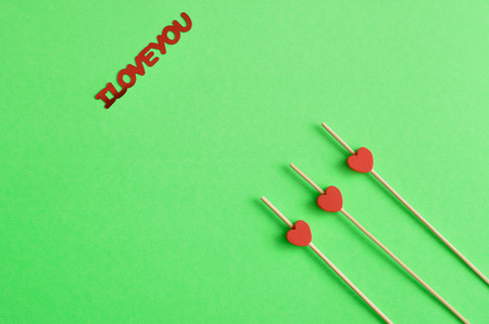 Valentines Day. Three red hearts on sticks with a green background an I love you in red lettering