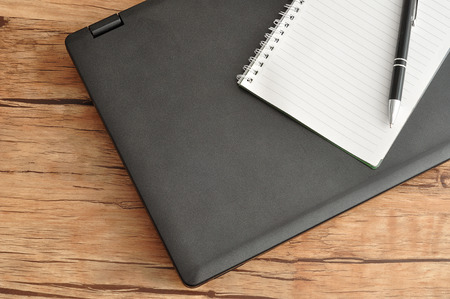 bussiness time: Laptop with a notebook and a pen