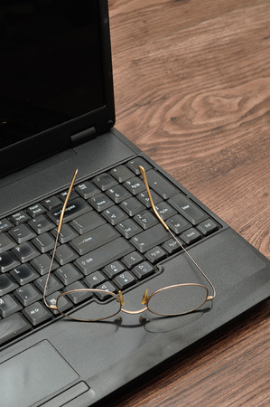 bussiness time: A laptop with reading glasses Stock Photo