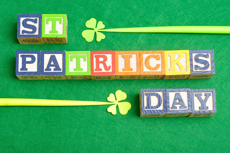 four leaf clovers: PreviewSave to a lightSt Patricks day spelled with colorful alphabet blocks displayed with two four leaf clovers on a green background