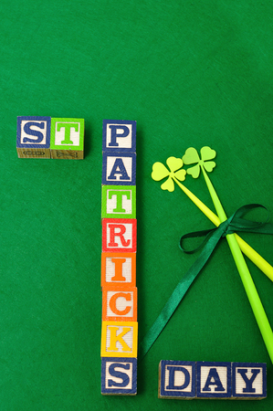 four leaf clovers: St Patricks day spelled with colorful alphabet blocks displayed with two four leaf clovers on a green background