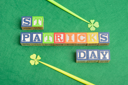 four leaf clovers: PreviewSave to a St Patricks day spelled with colorful alphabet blocks displayed with two four leaf clovers on a green background