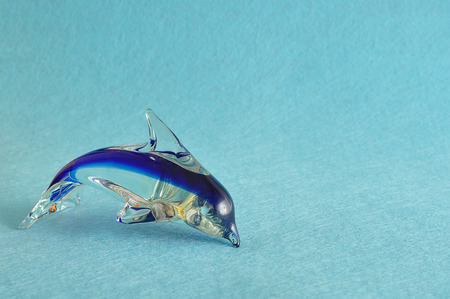 A glass dolphin figurine that is sold for souvenirs at various gift shops