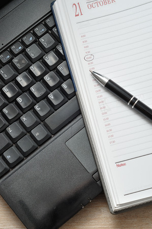 A laptop with a pen and an open diary