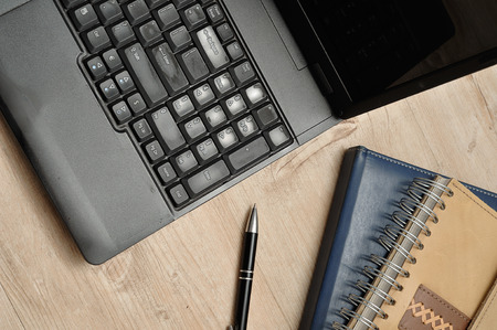 bussiness time: Laptop, a pen and notebooks