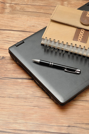 bussiness time: Laptop with a leather notebook and a pen