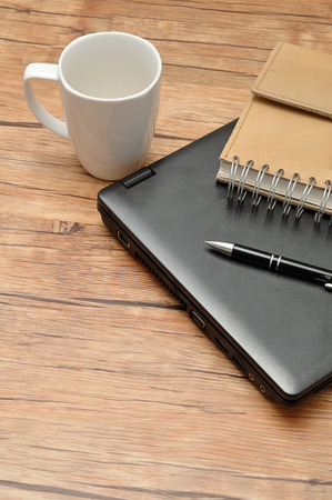 Laptop with a leather notebook, a pen and an empty white mug