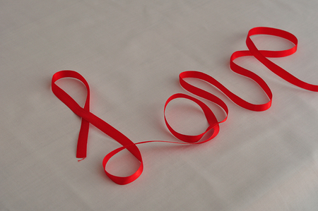 Love written with a red ribbon Stock Photo
