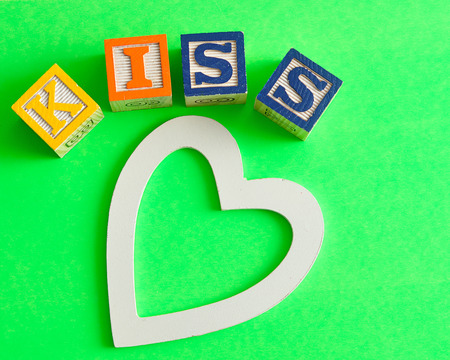 saint valentine   s day: Valentines Day.Kiss Spelled with colorful alphabet blocks and a white heart isolated on a green background Stock Photo