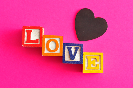 saint valentine   s day: Valentines Day.Love Spelled with colorful alphabet blocks and a black heart isolated on a pink background