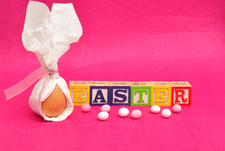 serviette: An egg tied in a serviette that looks like bunny ears for easter displayed with candy and alphabet blocks spelling easter on a pink background Foto de archivo