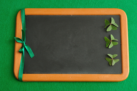 fourleaf: Clovers and a green ribbon displayed on a black board for St, Patricks day