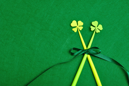 four leaf clovers: A four leaf clovers on a sticks tied together with a green bow isolated on a green background for St. Patricks day