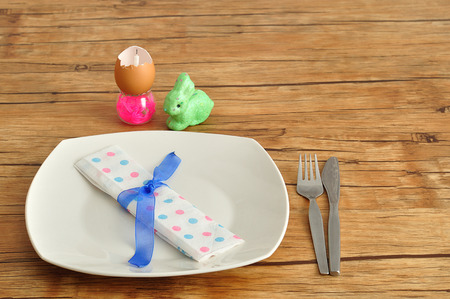consisting: A simple easter place setting consisting of a plate, knife, fork and dot napkin tied with a blue ribbon and some easter table decorations. Stock Photo